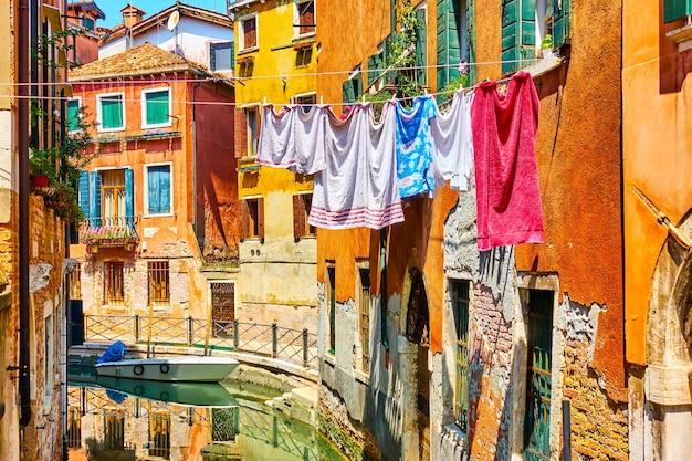 Casas antigas coloridas perto do canal de veneza com roupa de cama em um dia ensolarado, itália