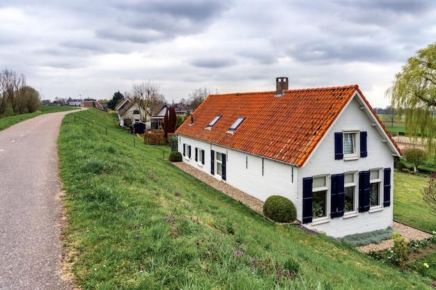 Casas atrás dos diques do rio perto de sleeuwijk