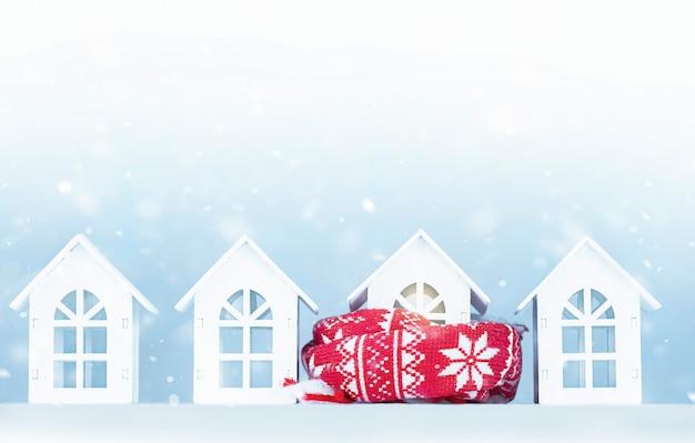 Casas brancas de brinquedo em uma fileira. uma casa está embrulhada em um lenço. conceito de negócios