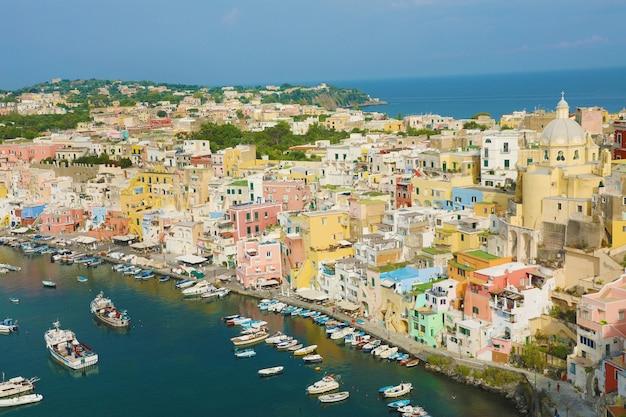 Casas coloridas, barcos de pesca e iates em marina corricella, ilha de procida, itália