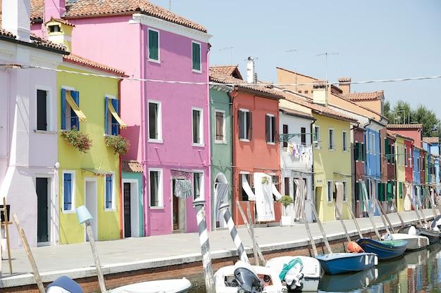 Casas coloridas e canal com barcos na ilha de burano, veneza, itália