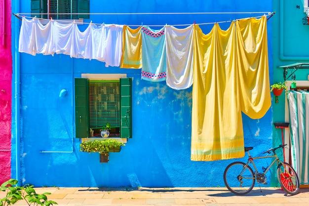 Casas coloridas em burano e roupas de cama na rua, veneza, itália