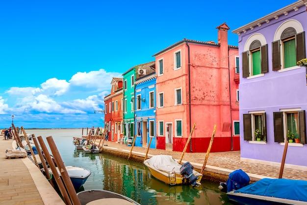 Casas coloridas em burano, perto de veneza, itália, com barcos e lindo céu azul no verão