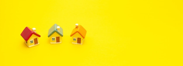 Casas coloridas em miniatura sobre um fundo amarelo, espaço para texto