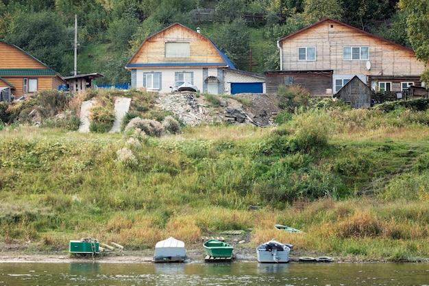 Casas de aldeia de madeira nas margens do rio. a beleza do interior da rússia. Foto Premium