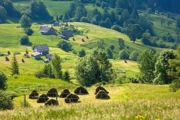 Casas de aldeia nas colinas com prados verdes em dia de verão