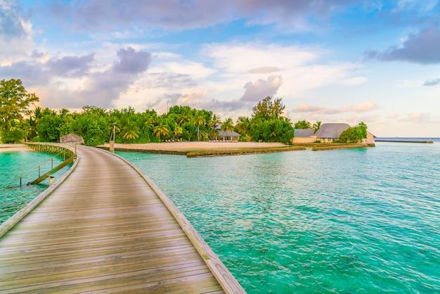 Casas de campo bonitas da água na ilha tropical de maldivas no tempo do por do sol.