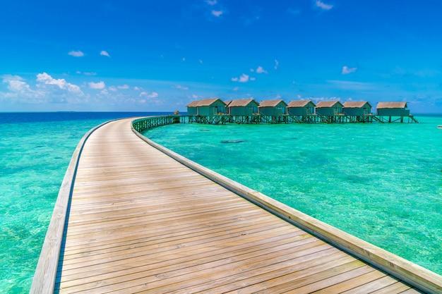 Casas de campo bonitas da água na ilha tropical de maldivas.