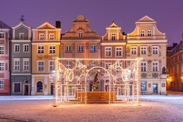 Casas de comerciantes e fonte decorada na praça do mercado velho na cidade velha na noite de natal, poznan