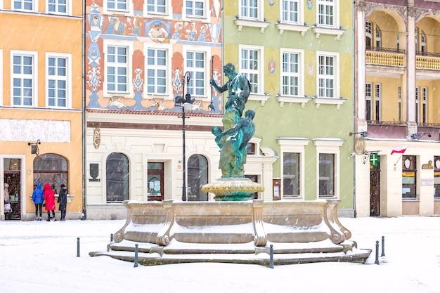 Casas de comerciantes e fonte na praça do mercado velho na cidade velha no dia nevado de inverno, poznan