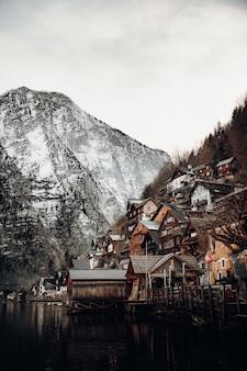 Casas de concreto marrons e brancas perto de uma montanha sob um céu branco durante o dia