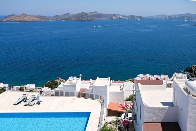 Casas de férias brancas em resort com vista para o mar e piscina e palmeiras.