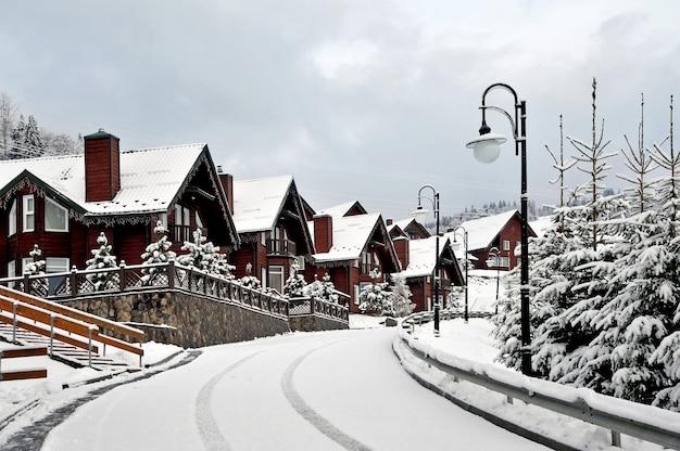 Casas de férias de madeira na estância de férias na montanha coberta de neve fresca no inverno. bela rua de inverno após a queda de neve.