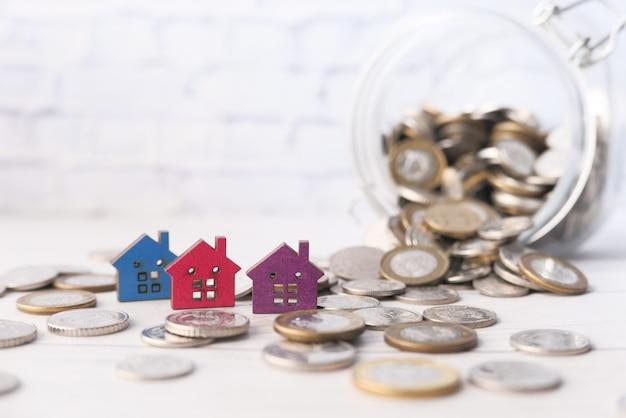 Casas de madeira coloridas e moedas em branco, o conceito de conceito de finanças
