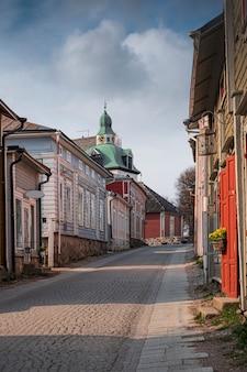 Casas de madeira coloridas em uma rua estreita no centro histórico da cidade com vista para a catedral de porvoo, na finlândia, em um dia ensolarado de primavera
