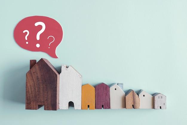 Casas de madeira com pontos de interrogação