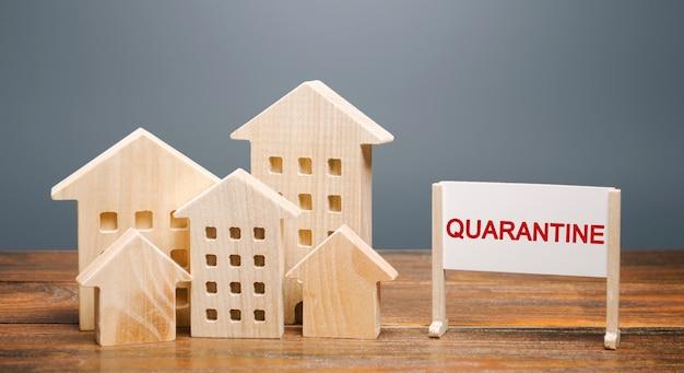 Casas de madeira e a inscrição quarentena em um cavalete. infecção pandêmica por coronavírus covid-19.