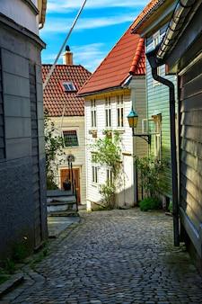 Casas de madeira e estrada de paralelepípedos, noruega