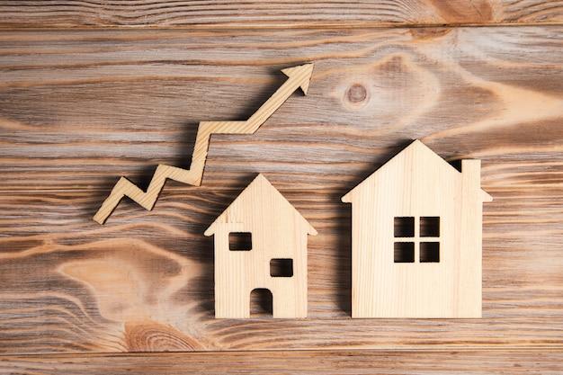 Casas de madeira e seta para cima. o conceito de crescimento do mercado imobiliário