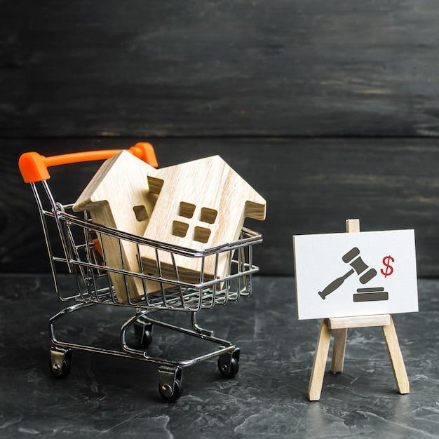 Casas de madeira em carrinho de supermercado para compra de moradias e prédios
