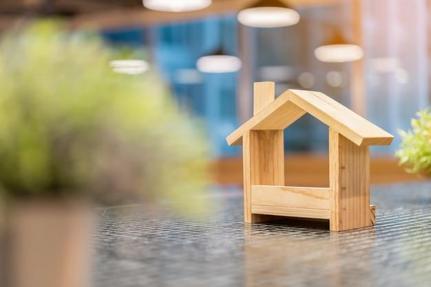 Casas de madeira em miniatura e plantas verdes de borrão em primeiro plano.