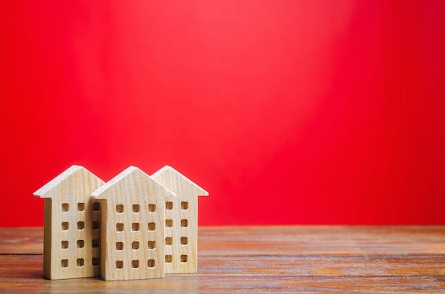 Casas de madeira em miniatura sobre um fundo vermelho. conceito imobiliário. cidade. aglomeração