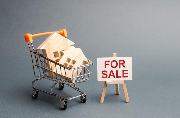 Casas de madeira em um carrinho de negociação e um stand com inscrição para venda