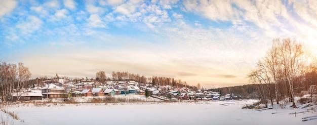 Casas de madeira nas margens do rio shokhonka coberto de neve em plyos na neve sob a luz do sol de inverno
