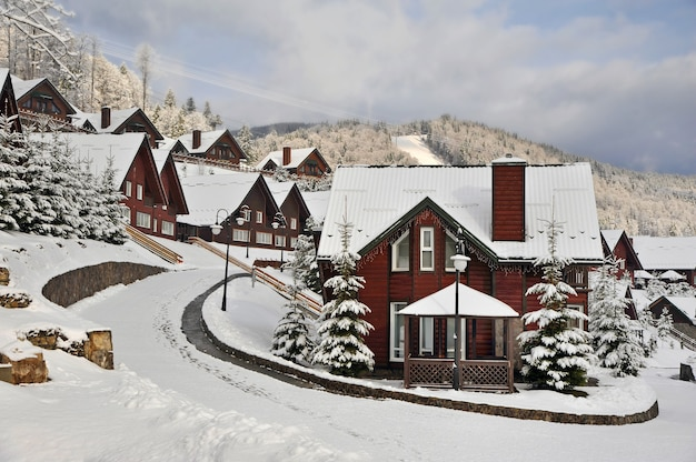 Casas de madeira tradicionais na encosta de uma colina nas montanhas dos cárpatos, rodeadas por pinheiros cobertos de neve.