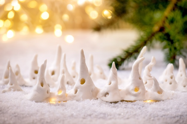 Casas de natal em porcelana. conjunto de casas de decoração de natal artesanais artesanais com janelas brilhantes na neve com luzes de férias de bokeh e galhos de árvores de abeto.