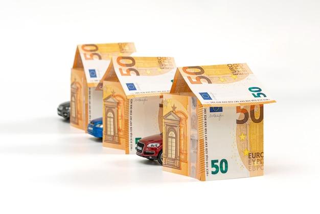 Casas de notas de euro e veículos isolados no branco. conceito de empréstimo, imobiliário e seguro automóvel