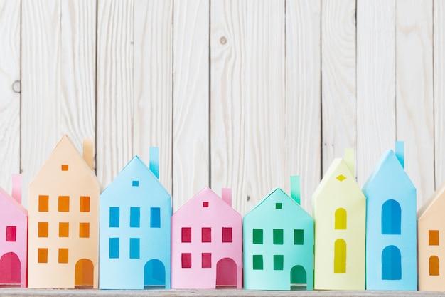 Casas de papel com fundo de madeira