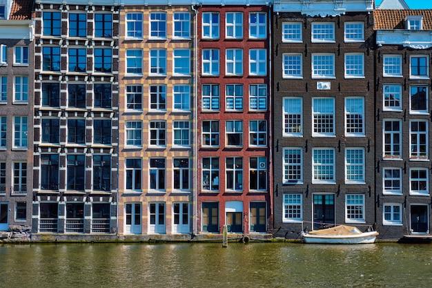 Casas e barcos no canal de amsterdã damrak com reflexão. ams