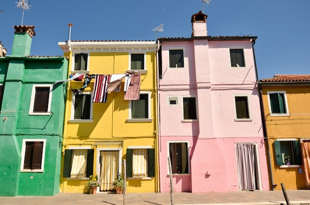 Casas em burano, veneza, itália. conceito colorido, amarelo, rosa e azul