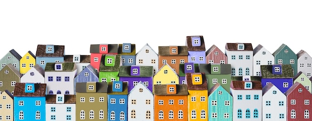 Casas em miniatura coloridas dispostas em fileiras isoladas em um fundo branco. banner de plano de fundo da cidade urbana. copie o espaço