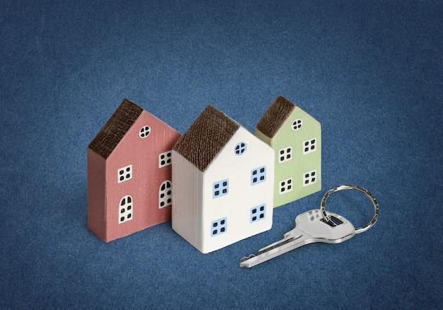 Casas em miniatura com a chave da casa em fundo de papel azul