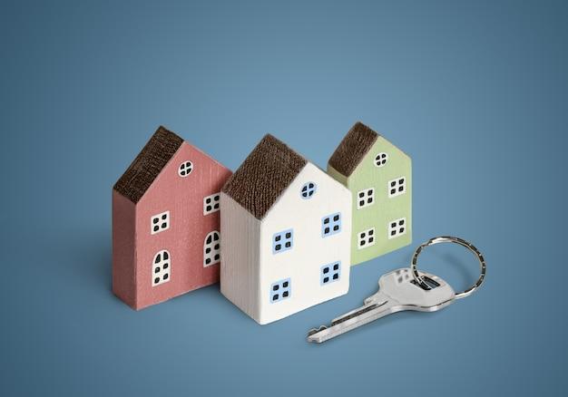 Casas em miniatura com chave de casa sobre fundo azul. copie o espaço