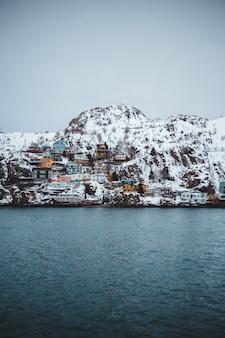 Casas em penhasco com vista do corpo d'água durante o dia