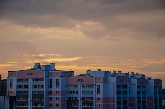 Casas enfadonhas de vários andares de uma cidade moderna ao fundo do pôr do sol