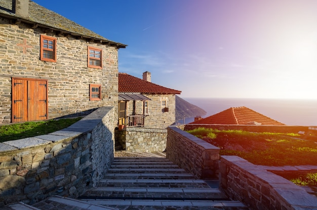 Casas gregas antigas com um telhado de azulejos e vista para o mar