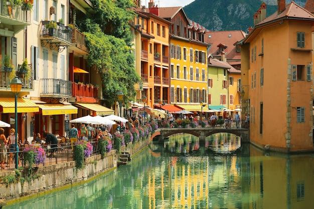 Casas medievais coloridas refletidas na água do canal em annecy