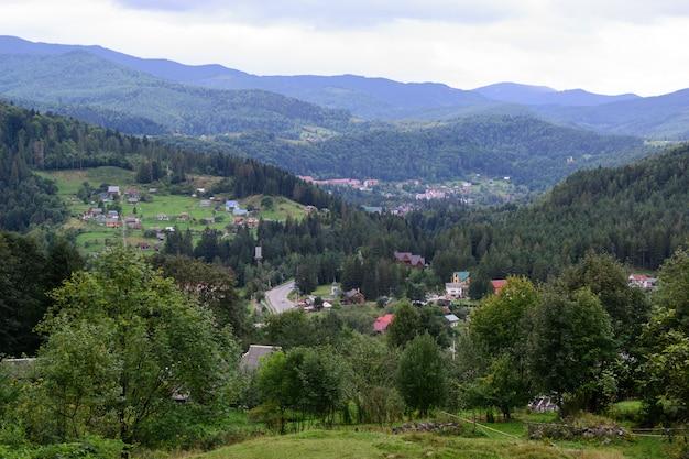 Casas no meio de uma paisagem de floresta e montanhas