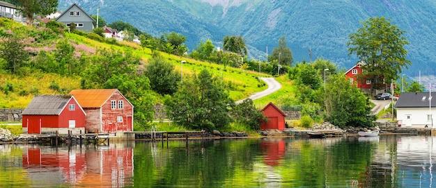 Casas rurais norueguesas de madeira na costa verde do fiorde, paisagem com vista para o mar
