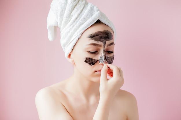 Casca cosmética da beleza. closeup linda fêmea jovem com casca preta máscara na pele