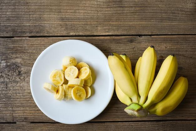 Casca de banana fatiada em prato branco e fundo de madeira, banana descascada pronta para comer
