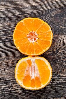 Casca de laranja descascada deitada sobre uma mesa de madeira, frutas cítricas Foto Premium