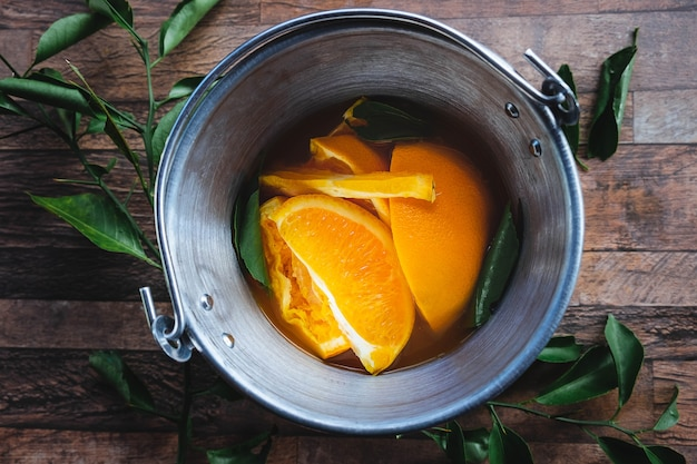 Casca de laranja e suco de laranja em um balde