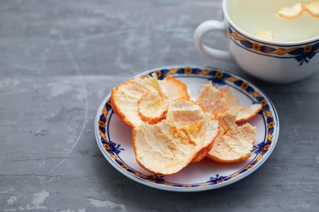 Casca de laranja no prato e em um copo com água quente