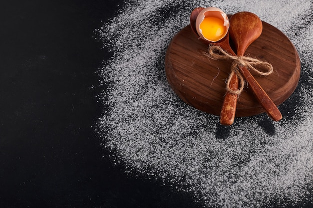 Casca de ovo com gema em uma colher de pau na travessa de madeira.