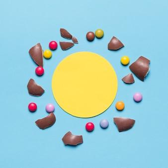 Casca de ovo de páscoa quebrado e pedras preciosas cercadas com frame circular amarelo em branco contra o fundo azul